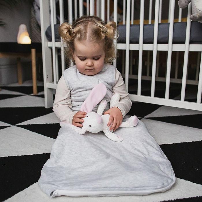 Baby in grey sleepbag holding soft toy
