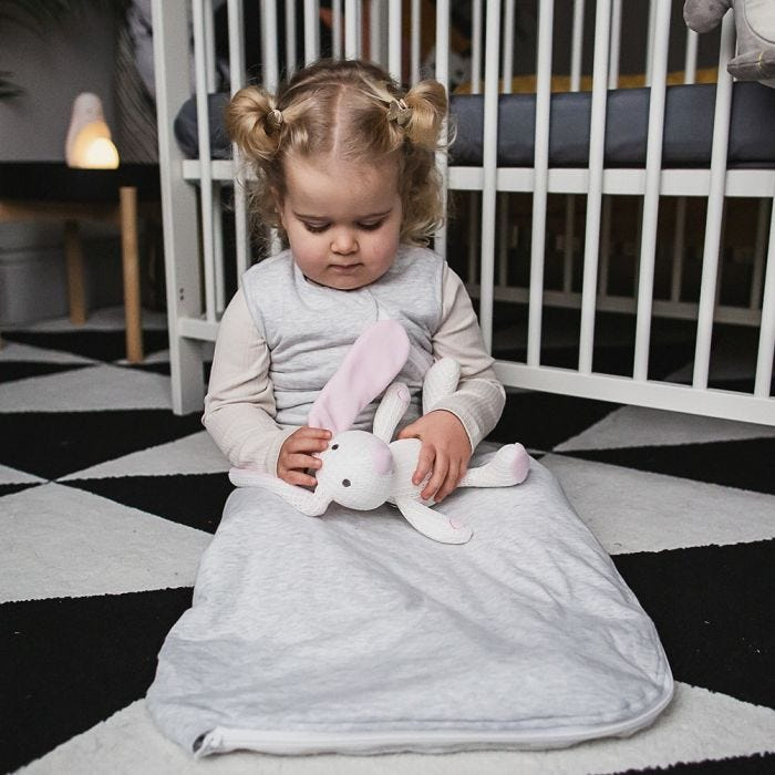 Baby in grobag playing with soft toy