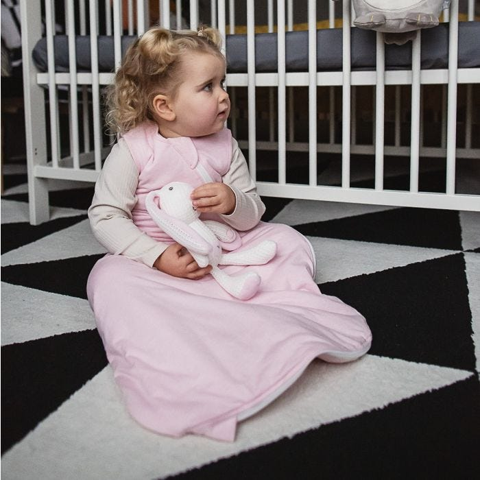 Baby in pink grobag playing with soft toy