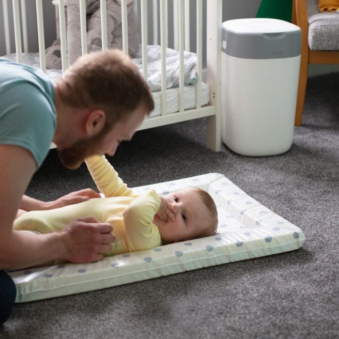 Dad playing with baby on changing mat with Twist & Click Nappy Disposal Bin in the background adjacent to the cot