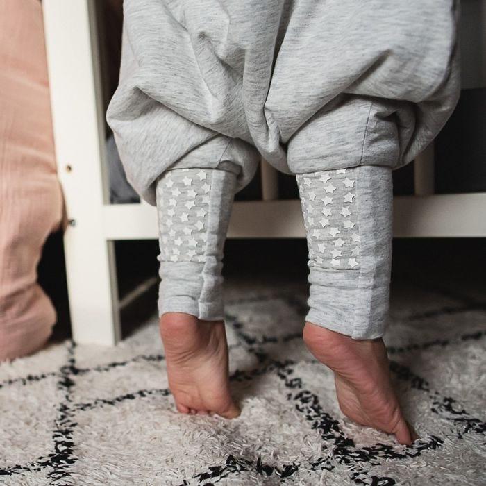 Baby standing wearing The original grobag grey marl steppee