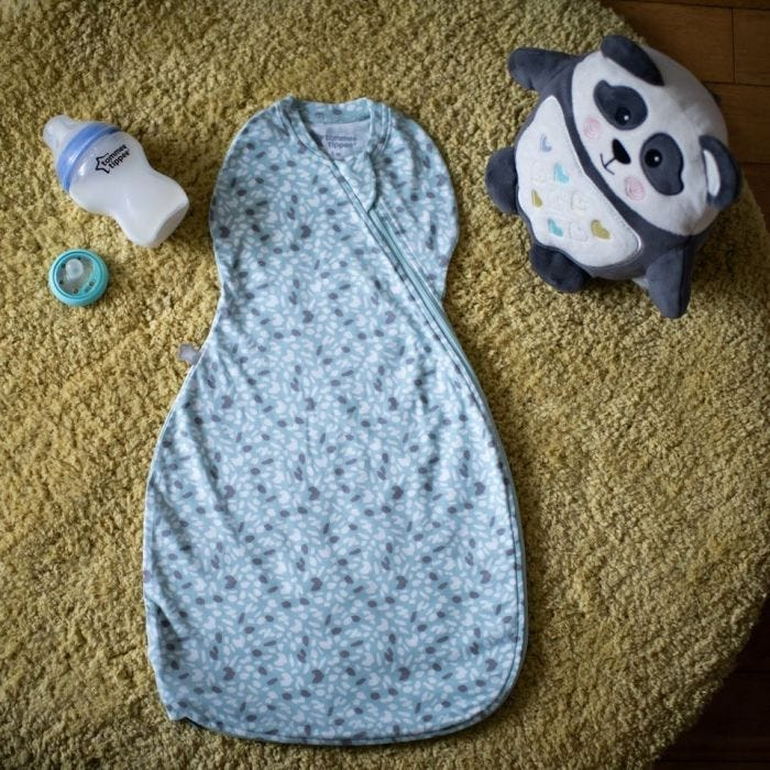 The Original Grobag Earth Green Easy Swaddle on floor with grofreind and closer to nature bottle