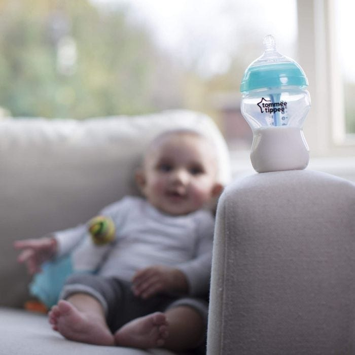 advanced anti colic baby bottle on sofa with baby in background