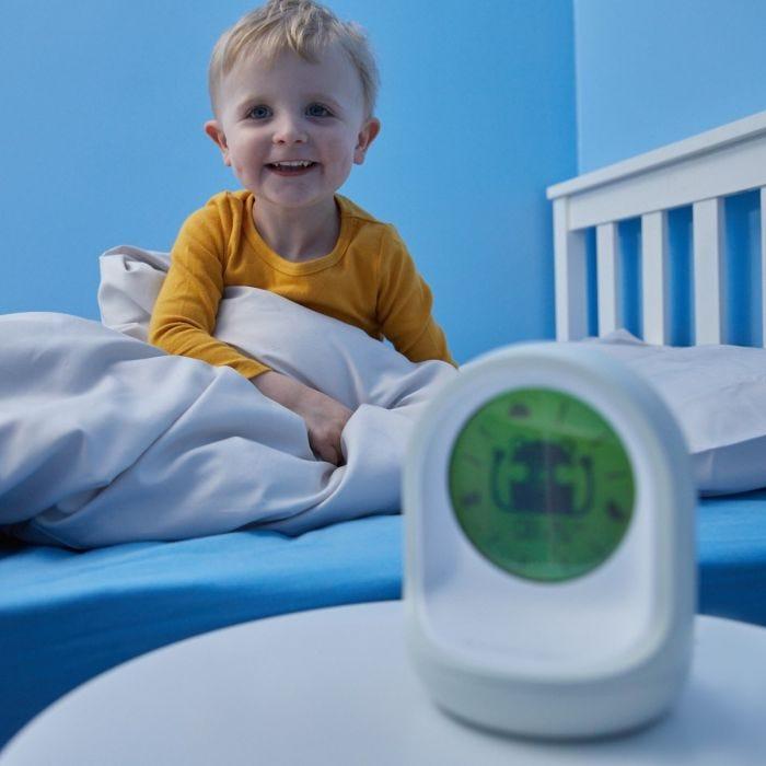 child smiling behind tommee tippee sleep trainer