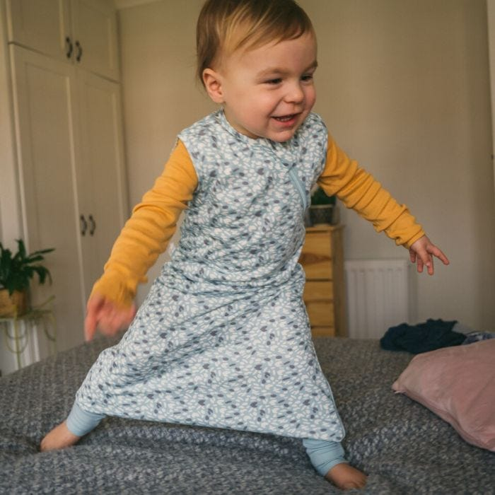 Baby wearing The Original Grobag Earth Green Steppee while standing on a bed