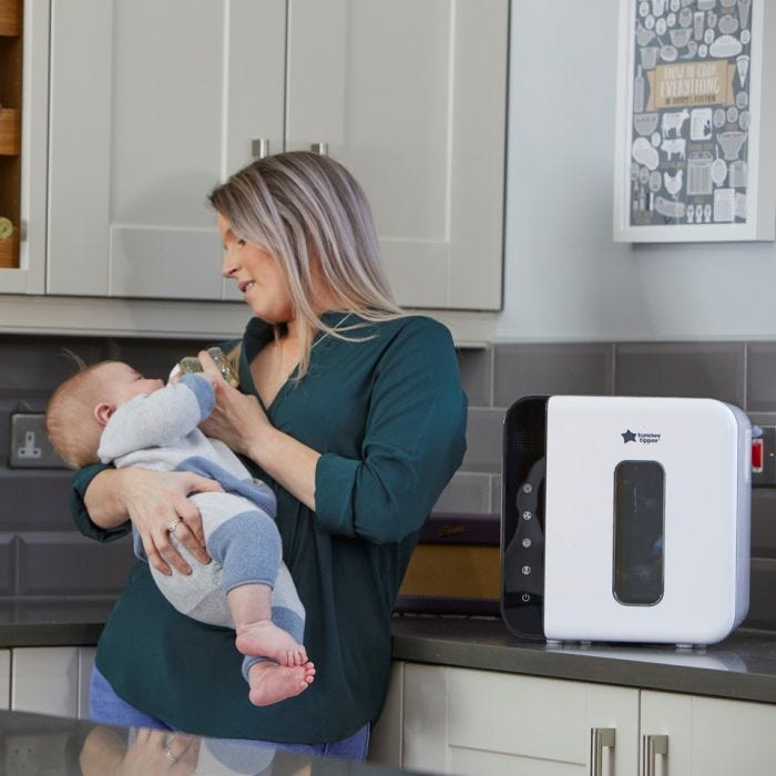 Tommee Tippee Ultra UV 3-in-1 Steriliser, Dryer and Storage in kitchen with mum feeding baby