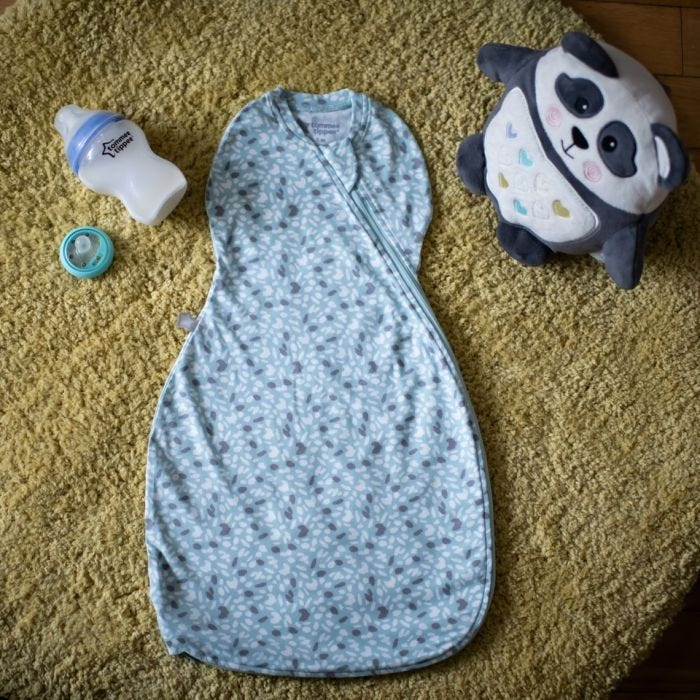 Tommee Tippee Earth Green Easy Swaddle in nursery with baby bottle and pip the panda
