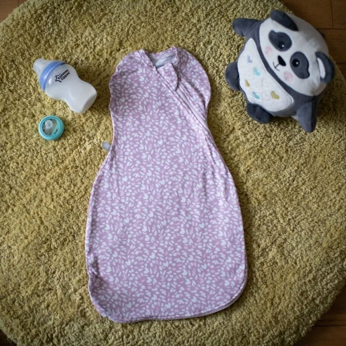Tommee Tippee Earth Grape Easy Swaddle on ground with baby bottle and pip the panda