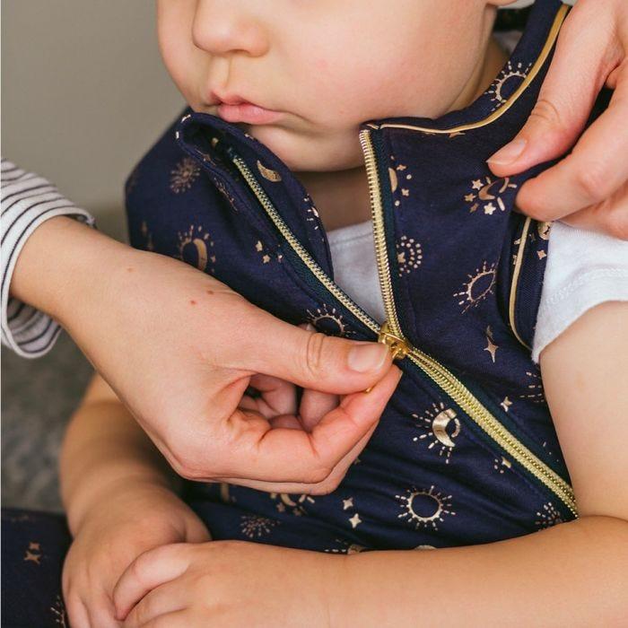Baby wearing The Original Grobag Moon Child Sleepbag with mum pulling up zip