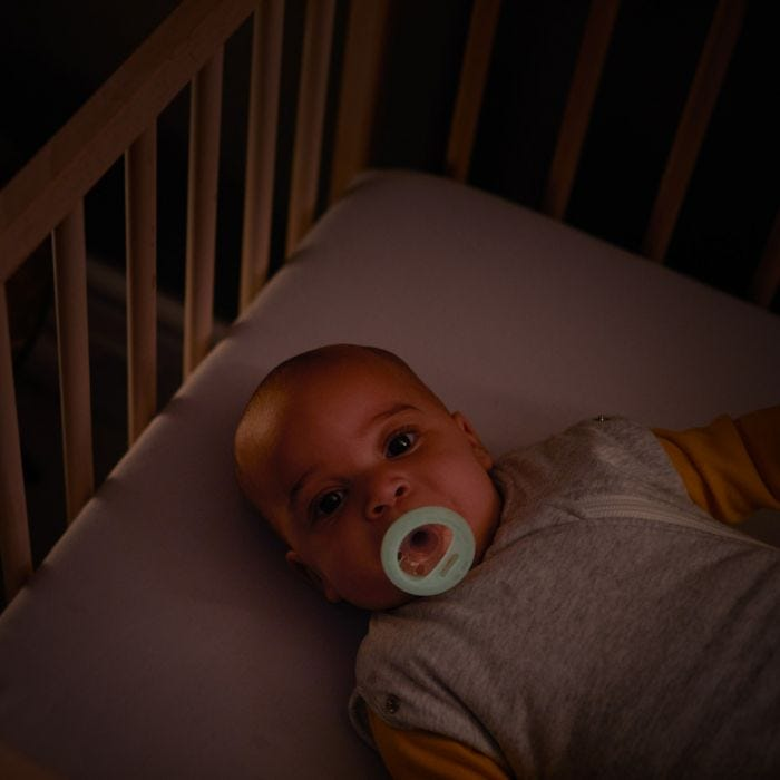 Baby lying in cot with Breast-like Night Time Soother in mouth