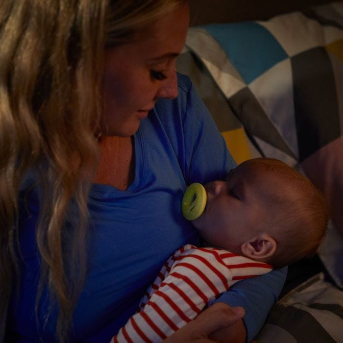 Mum holding baby who is holding Breast-like Night Time Soother