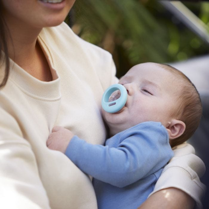 Baby using Closer to Nature Breast-like Pacifier in mums arms