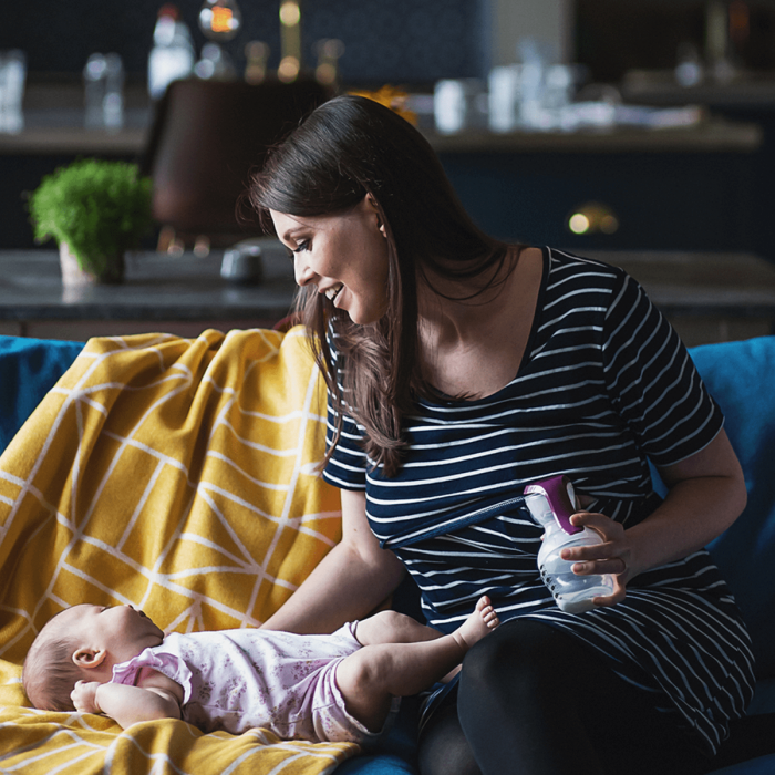 mum expressing with manual breast pump while playing with baby