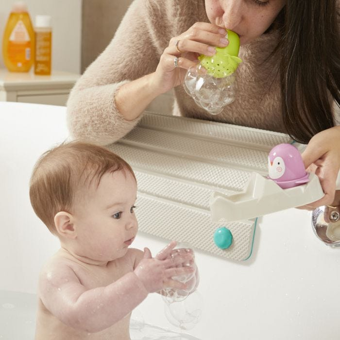 mum blowing bubbles for baby in the bath