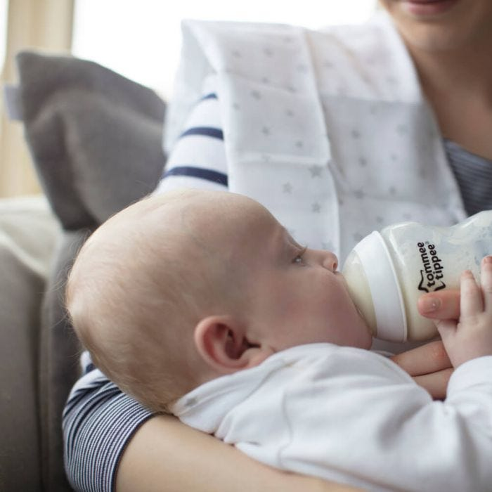 Mum feeding baby with Tommee Tippee bottle of milk