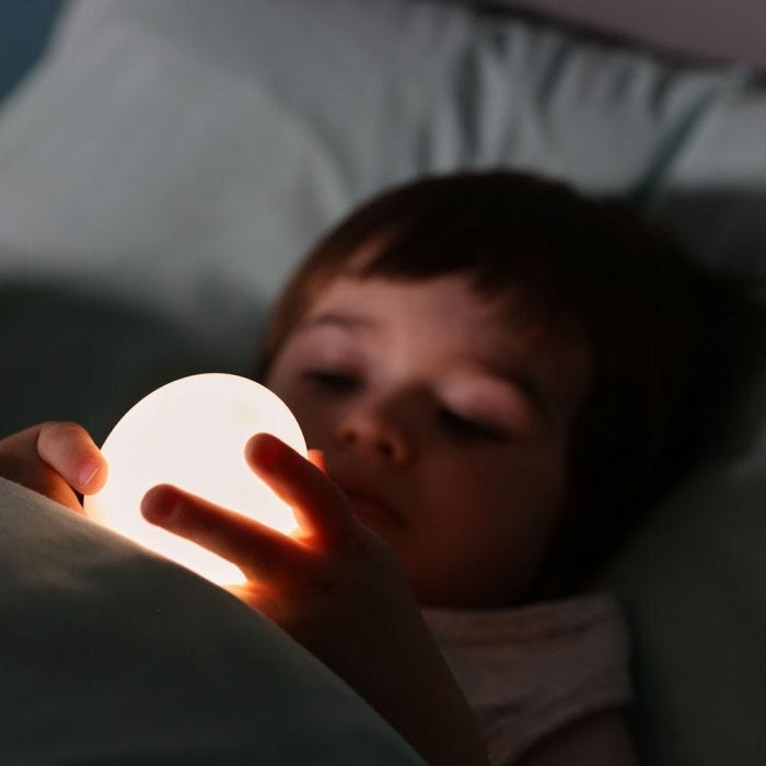 child reading with Penguin Night Light