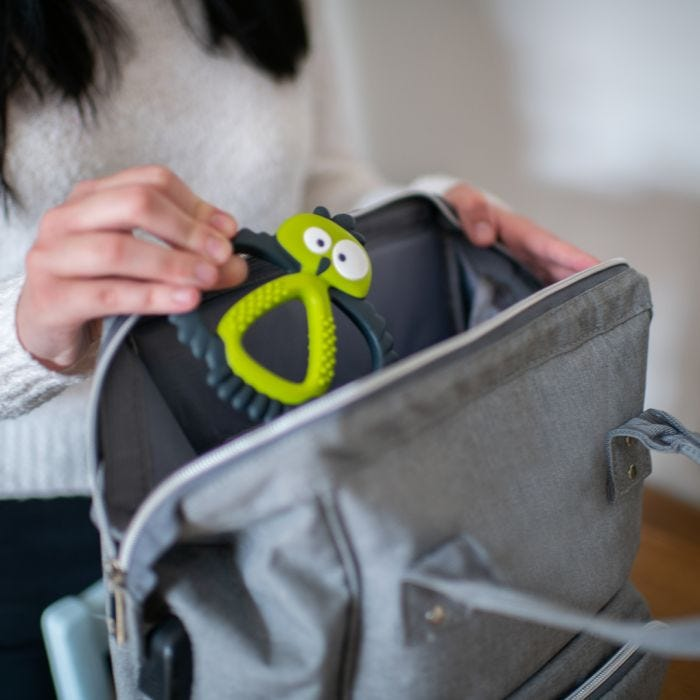 mum placing maxi teething toy in bag