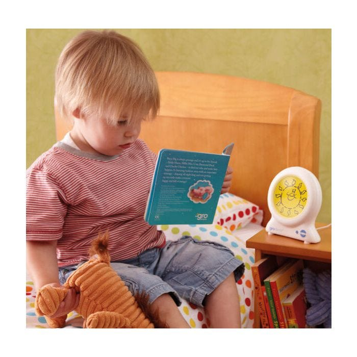 Child reading story book with Groclock sleep trainer