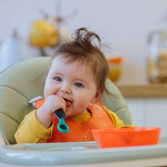 baby holding smushee first self feeding spoon