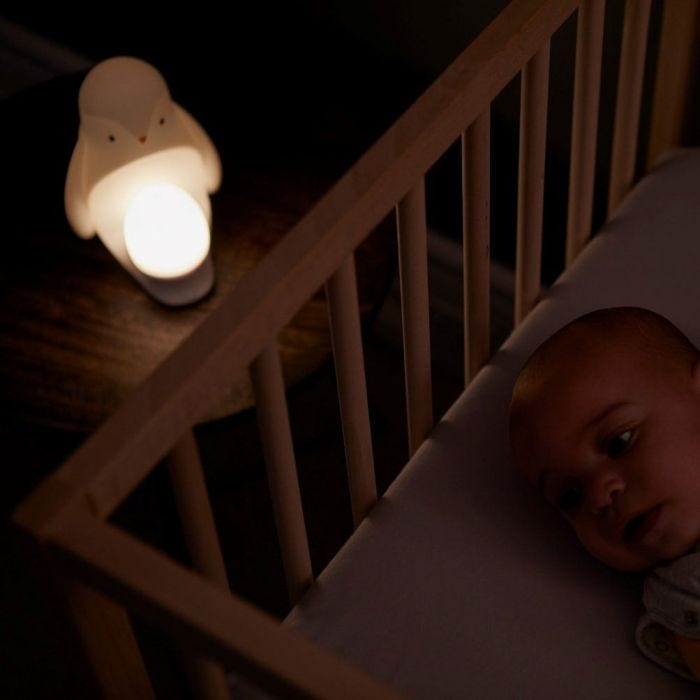 Penguin Night Light at the side of the cot with baby lying inside