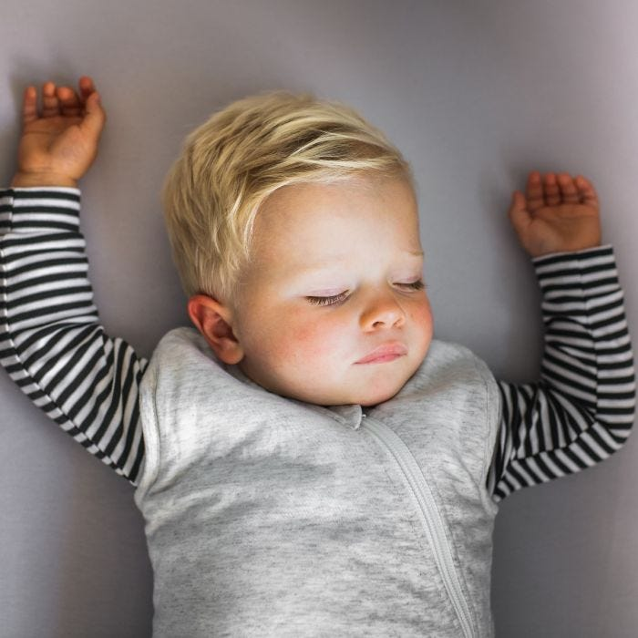 Child sleeping in The Original Grobag Grey Marl Sleepbag