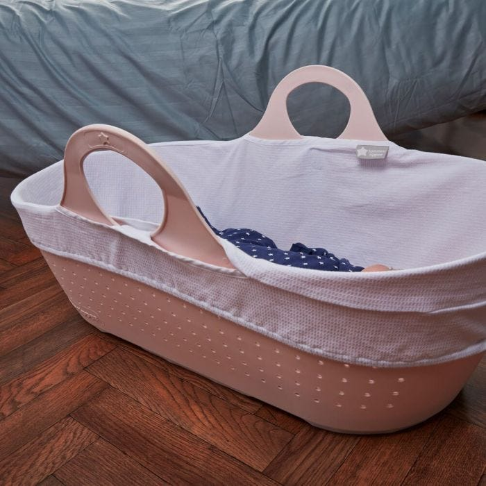 pink moses basket on floor