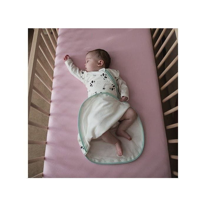 Baby in cot with arm on wearing snuggle