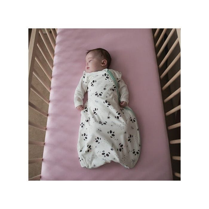 Baby in cot with arms in wearing snuggle