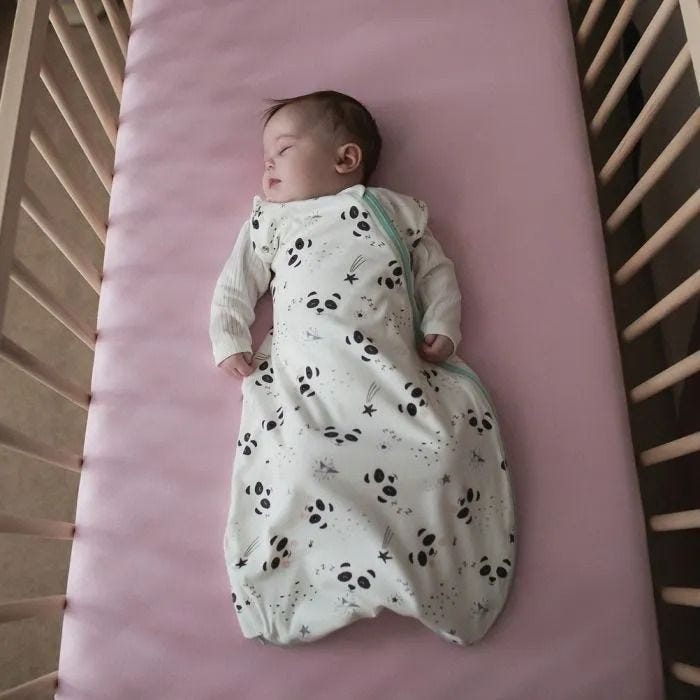Baby girl lying in cot wearing the Pip the Panda Grobag Snuggle
