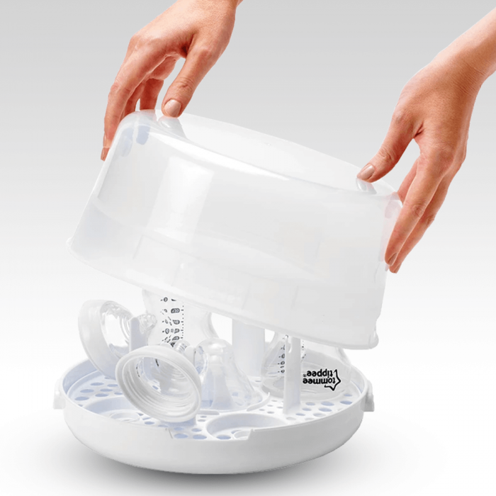 putting-lid-onto-micro-steam-steriliser-that-contains-bottles-and-teats