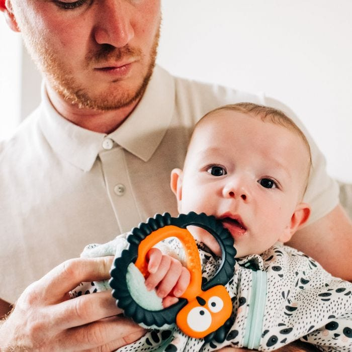 baby holding maxi teething toy