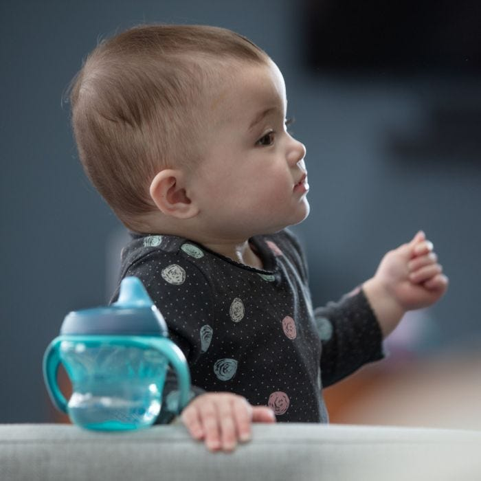 Baby with cup in foreground