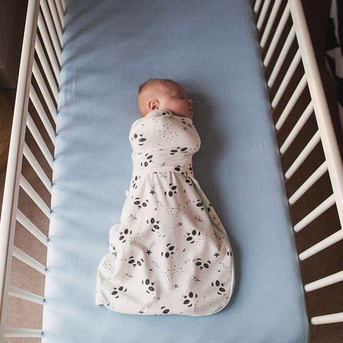 Baby in cot wearing Little Pip Swaddle Wrap