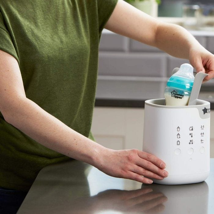 mum placing bottle in the 3-in-1 Advanced Electric Bottle and Pouch Warmer