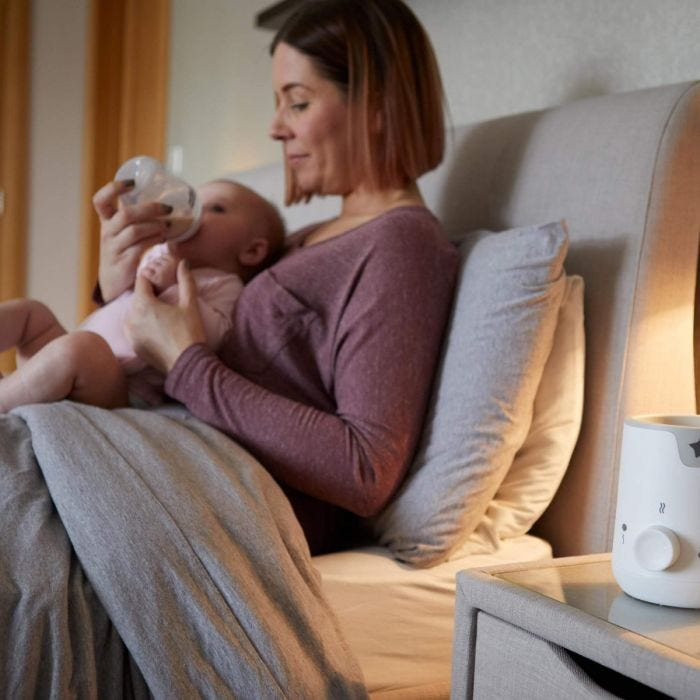 mum feeding baby with easi-warm bottle and food warmer at the side of the bed