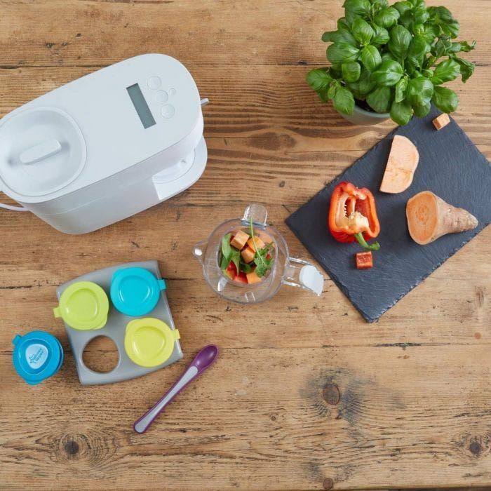 top-down-shot-of-quick-cook-baby-food-maker-with-a-range-of-fresh-cooking-ingredients-on-a-chopping-board-including-sweet-potato-and-pepper