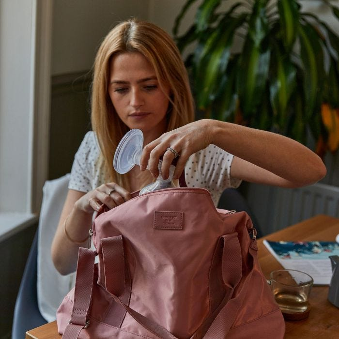 Mum putting manual breast pump in bag