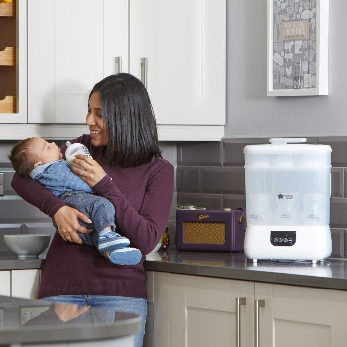 Mom feeding baby with Advanced Electric Steri-dryer in the background