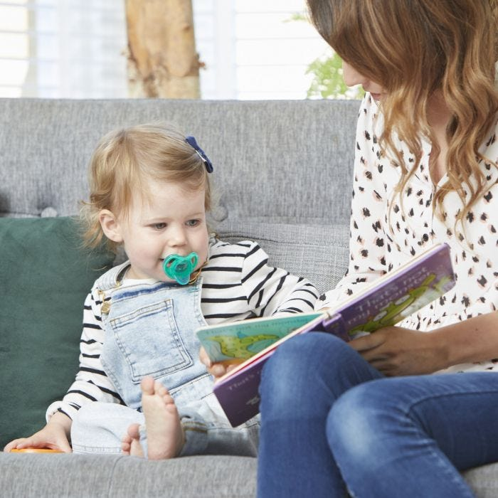 baby with an ultra-light soother and mum reading a book together
