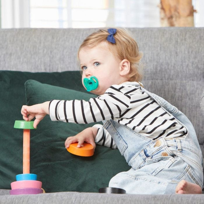 baby playing holding soother