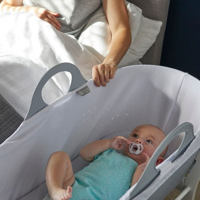 baby holding soother in moses basket
